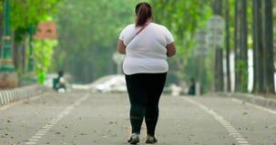 Femme de poids excessif marchant sur la rue au parc banque de vidéos