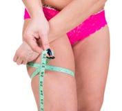 Femme de poids excessif mesurant son corps Photo stock
