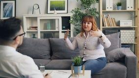 Femme de poids excessif parlant au thérapeute et souriant pendant la consultation dans la clinique banque de vidéos