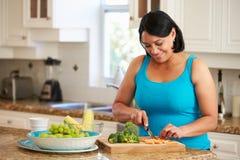 Femme de poids excessif préparant des légumes dans la cuisine image libre de droits