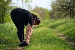 Femme de poids excessif r?chauffant des jambes avant le fonctionnement photographie stock libre de droits