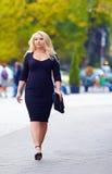Femme de poids excessif sûre marchant la rue de ville photos stock