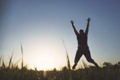 Femme de poids excessif sautant au fond de ciel de coucher du soleil Photos stock
