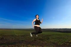 Femme de poids excessif sautant dans le pré Image stock