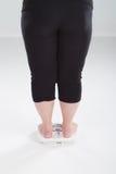 Femme de poids excessif sur l'échelle Photos libres de droits