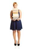 Femme de poids excessif tenant des livres Photos libres de droits
