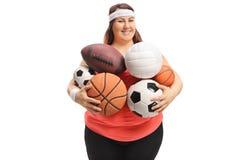 Femme de poids excessif tenant différents genres de boules de sports images stock