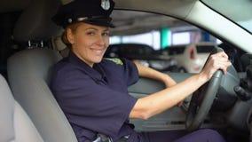 Femme de police dans l'uniforme se reposant dans la voiture de patrouille et souriant à la caméra, en service clips vidéos