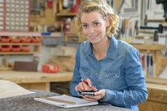 Femme de portrait dans l'atelier utilisant la calculatrice Photographie stock libre de droits