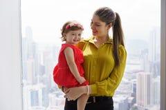 Femme de portrait dans la carrière avec le petit bébé dans le bureau Image libre de droits