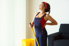 Femme de portrait faisant des corvées nettoyant le plancher avec le mal de dos image libre de droits