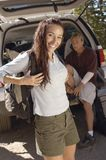Femme de portrait se tenant avec l'ami s'asseyant dans la botte de voiture Photos libres de droits
