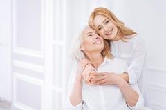 Femme de Posditive et sa fille adulte se reposant à la maison Photo stock