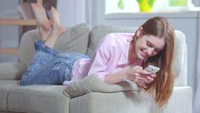 Femme de Preety détendant sur des sms d'écriture de sofa banque de vidéos