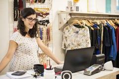 Femme de Pregenant orking dans le magasin de vêtements Images libres de droits