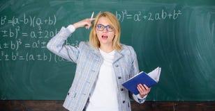 Femme de professeur expliquer pr?s du tableau Le ma?tre d'?cole expliquent des choses bien et font int?ressant soumis pertinent image libre de droits