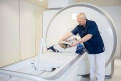 Femme de Putting Headphones On de radiologue subissant le balayage d'IRM photo libre de droits