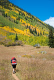 Femme de randonneur avec la montagne rocheuse de grand sac à dos images stock