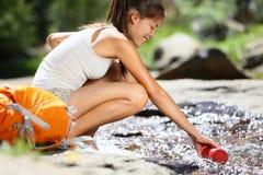 Femme de randonneur prenant l'eau en rivière dans Yosemite Photographie stock libre de droits