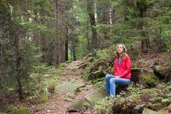 Femme de randonneur s'asseyant sur un arrêt dans la forêt Images libres de droits