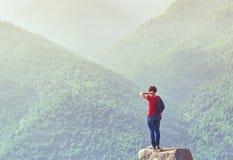 Femme de randonneur se tenant sur la roche au lever de soleil Photo stock