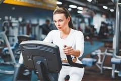 Femme de recyclage d'intérieur faisant la cardio- séance d'entraînement faisant du vélo sur à l'intérieur le vélo de gymnase Photos libres de droits
