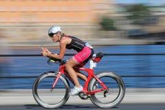 Femme de recyclage rapide sur le vélo de emballage rouge avancé Image stock