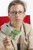 Femme de regard sérieux avec cents notes d'euro Photo stock