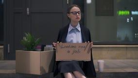 Femme de renversement s'asseyant avec le carton recherchant un signe du travail dans la rue banque de vidéos