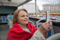 Femme de retraité prenant des photos par le téléphone dans l'autobus touristique Images stock