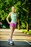 Femme de Rollerblading Le jeune modèle femelle attrayant de forme physique est ha Photographie stock libre de droits