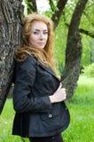 Femme de roux près d'arbre image stock