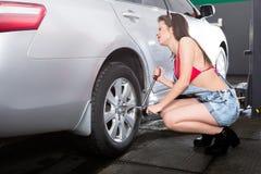 Femme de service de pneu Photographie stock