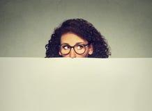 Femme de signe de bannière jetant un coup d'oeil au-dessus du bord du panneau d'affichage vide vide avec l'espace de copie pour l Photos stock