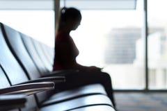Femme de silhouette dans la salle d'attente d'aéroport Photographie stock