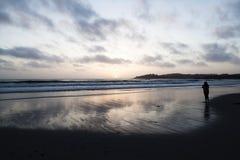 Femme de silhouette se tenant sur la plage au coucher du soleil Photo libre de droits