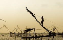 Femme de silhouette sur l'outil de pêche au coucher du soleil Photo stock