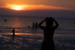 Femme de silhouette sur la plage avec le coucher du soleil Photographie stock libre de droits