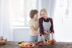 Femme de soin joyeuse aidant son amie Image stock