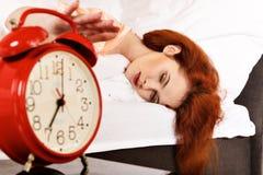 Femme de sommeil avec son réveil émouvant de main Image stock
