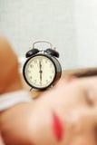 Femme de sommeil avec une horloge d'alarme. Image stock