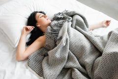 Femme de sommeil de brune couverte de couverture grise image stock