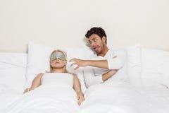 Femme de sommeil de taquinerie de jeune homme fâché dans le lit Photographie stock libre de droits