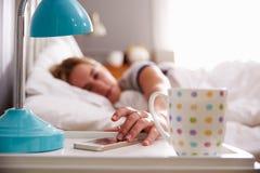 Femme de sommeil réveillé par le téléphone portable dans la chambre à coucher photographie stock