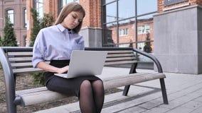 Femme de sommeil s'asseyant en dehors du bureau avec l'ordinateur portable dans son recouvrement photo stock