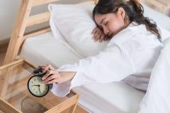 Femme de sommeil sa main touchant outre du réveil Images libres de droits