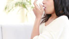 Femme de sourire à l'aide de l'inhalateur d'asthme à la maison clips vidéos