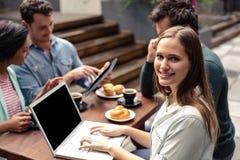 Femme de sourire à l'aide de l'ordinateur portable à la barre Images stock
