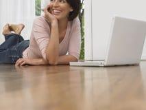Femme de sourire à l'aide de l'ordinateur portable sur le plancher en bois Image libre de droits