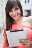 Femme de sourire à l'aide du comprimé numérique photo libre de droits